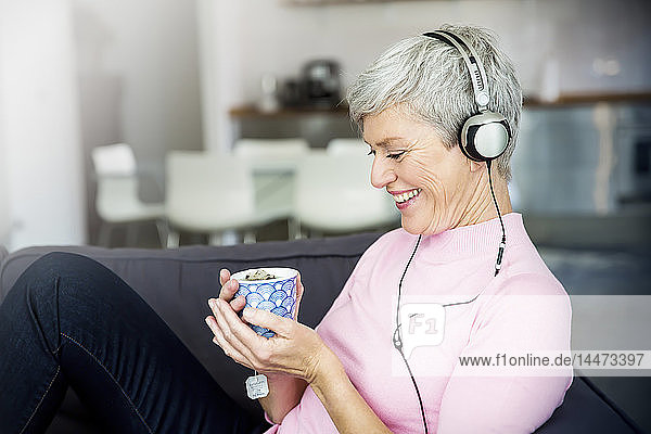 Laughing mature woman sitting on couch with cup of tea listening music with headphones