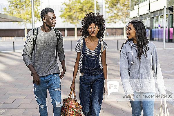 Drei Freunde spazieren durch die Stadt