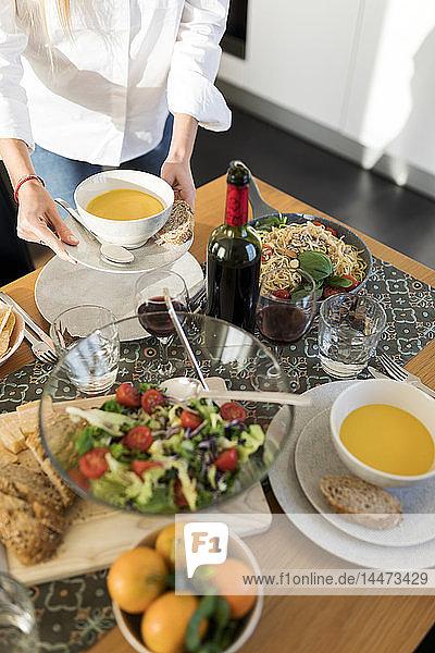 Junge Frau bereitet Tisch für ein Mittagessen mit Freunden vor