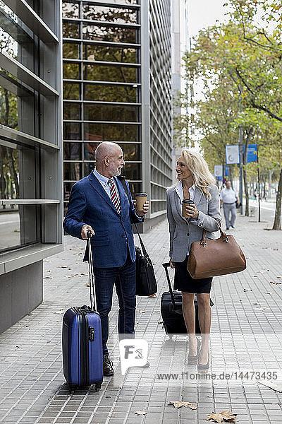 Leitender Geschäftsmann und Geschäftsfrau mit Gepäck unterwegs in der Stadt