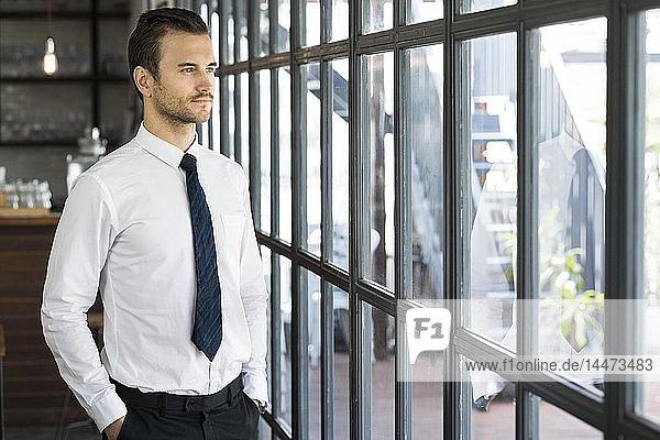 Zuversichtlicher Geschäftsmann schaut aus dem Fenster