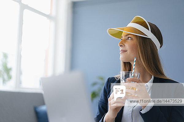 Porträt einer jungen Geschäftsfrau  die im Büro sitzt und von einem Urlaub träumt