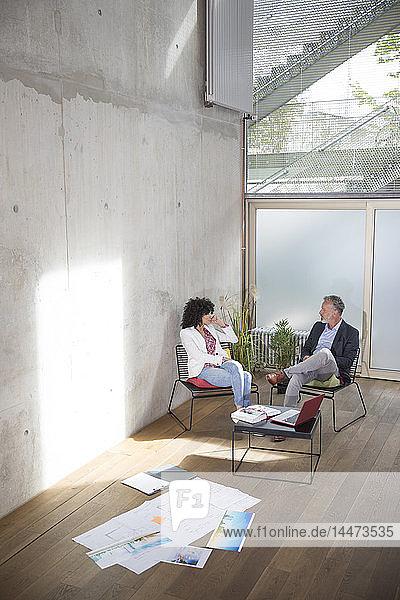 Geschäftsmann und Geschäftsfrau unterhalten sich in einem Loft mit Dokumenten auf dem Boden