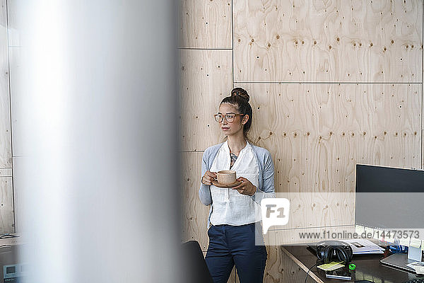Junge Frau  die im Kreativbüro arbeitet  eine Pause macht und Kaffee aus einer Holztasse trinkt