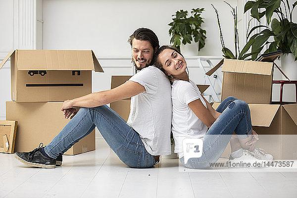 Glückliches Paar mit Pappkartons auf dem Boden sitzend in neuer Wohnung