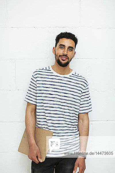 Portrait of smiling young man with clipboard at brick wall