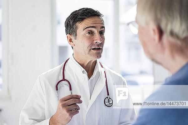 Porträt eines Arztes und Gespräch mit einem Patienten in der medizinischen Praxis