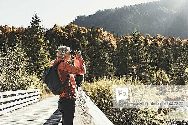 Österreich  Alpen  Frau auf Wanderung  die durch ein Fernglas schaut