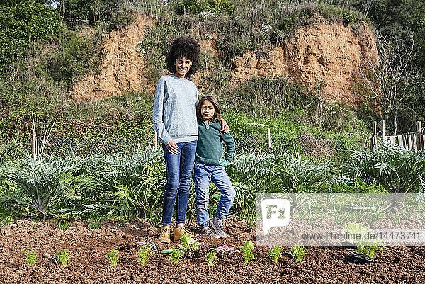 Mutter und Sohn stehen im Gemüsegarten mit Salatsetzlingen