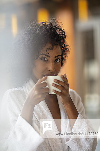 Portrait of young woman drinking coffee in spa