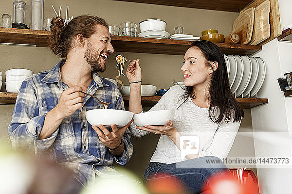 Happy couple sitting in kitchen  eating spaghetti