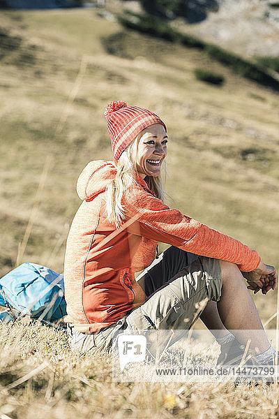 Österreich  Tirol  lächelnde Frau auf Almwiese sitzend
