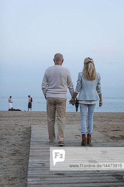 Spanien  Barcelona  Rückansicht eines älteren Ehepaars  das in der Abenddämmerung Hand in Hand am Strand spazieren geht
