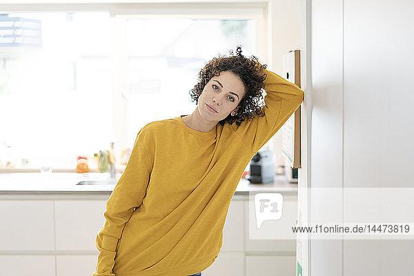 Porträt einer Frau  die zu Hause an einer Wand lehnt