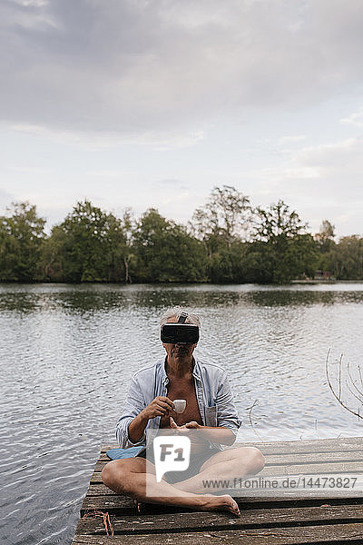 Senior man sitting on jetty at a lake wearing VR glasses and drinking coffee