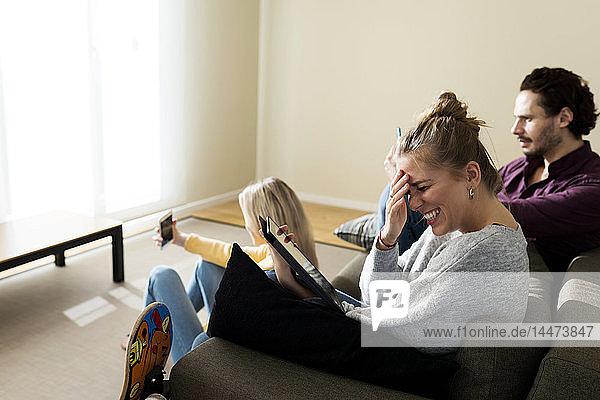 Freunde sitzen auf der Couch im Wohnzimmer und benutzen digitale Geräte