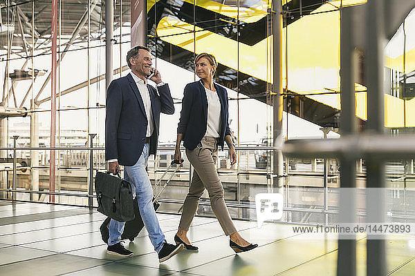 Geschäftsmann am Handy und Geschäftsfrau zu Fuß am Flughafen