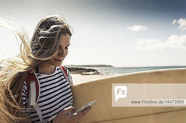 Young woman on the beach  carrying surfboard  using smartphone