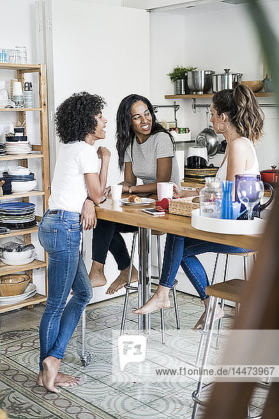 Three happy women socializing at kitchen table at home