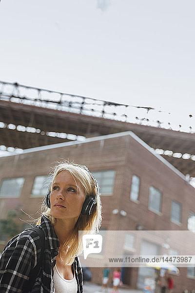 USA  New York City  Brooklyn  junge Frau  die in der Stadt mit Kopfhörern Musik hört und sich umsieht