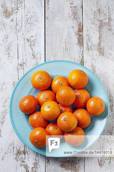 Mandarinen auf blauer Platte auf Holzgrund