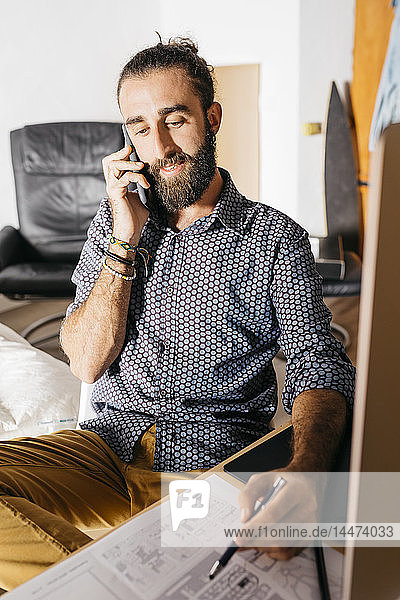 Young architect working at home with blueprints while talking on the phone