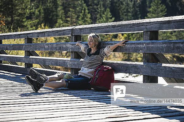 Österreich  Alpen  Frau auf einer Wanderung mit Pause auf einer Brücke sitzend