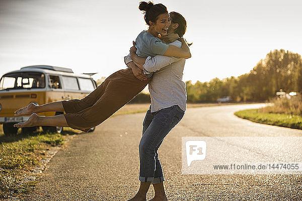 Glückliches Paar  das mit einem Wohnmobil unterwegs ist und sich auf der Straße umarmt