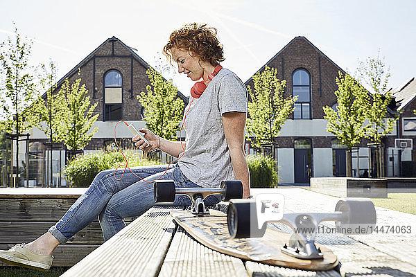 Lächelnde junge Frau mit Kopfhörern und Longboard mit Smartphone in städtischer Umgebung