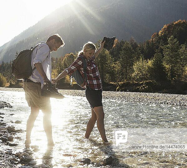 Österreich  Alpen  Ehepaar auf einer Wanderung watend in einem Bach