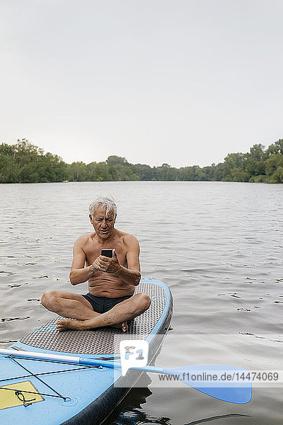 Älterer Mann sitzt mit seinem Handy im SUP-Board auf einem See