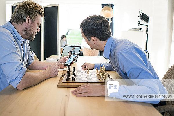 Zwei Männer spielen Schach und checken Smartphone