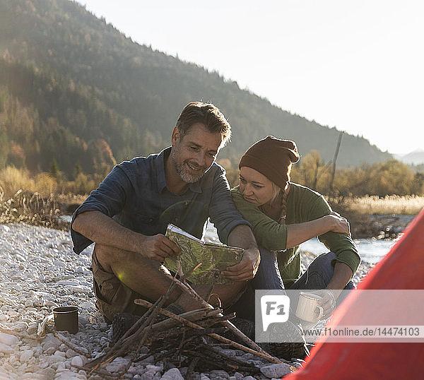 Älteres Paar zeltet am Flussufer und schaut auf die Karte