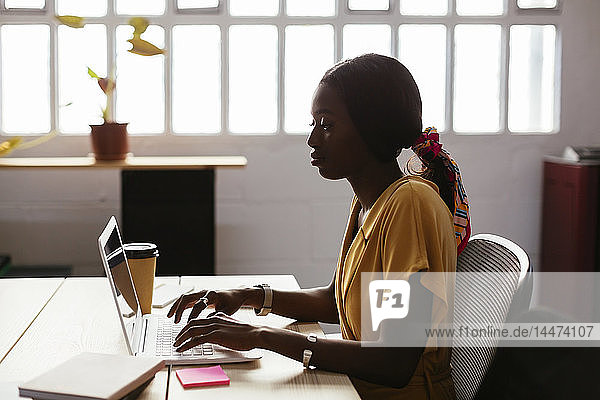 Young woman using laptop at desk in office