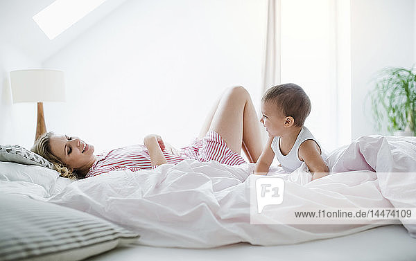 Smiling mother and toddler son lying in bed at home