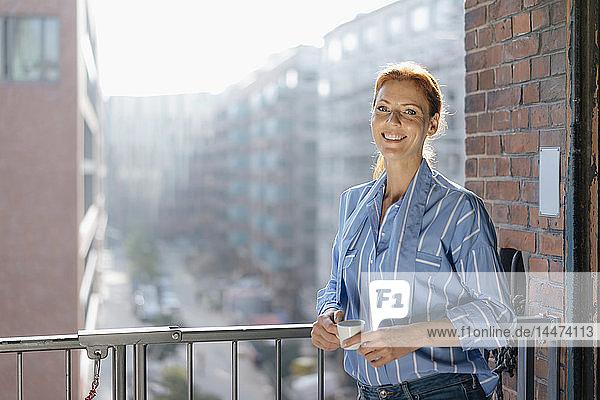 Deutschland  Hamburg  Speicherstadt  lächelnde Geschäftsfrau mit Tasse Kaffee am Fenster stehend mit Blick auf die Stadt