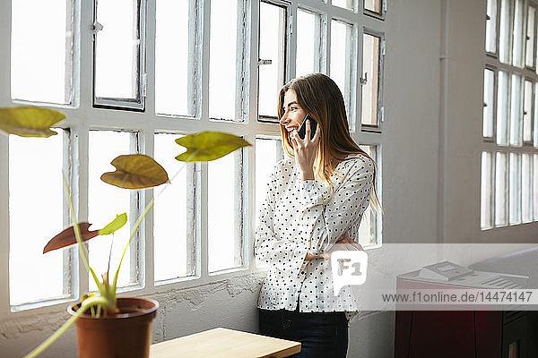 Glückliche junge Frau am Handy am Fenster im Büro