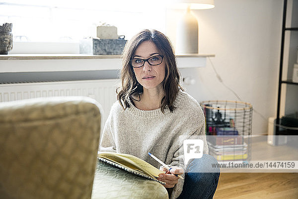 Woman sitting on floor  journalising in her diary