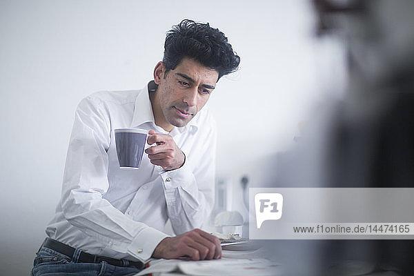 Porträt eines Geschäftsmannes  der morgens zu Hause Kaffee trinkt und Zeitung liest