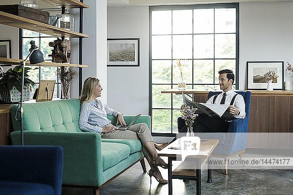 Geschäftskollegen mit Laptop und Zeitung im Coworking Space