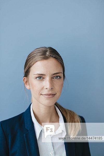 Porträt einer jungen Geschäftsfrau vor blauem Hintergrund
