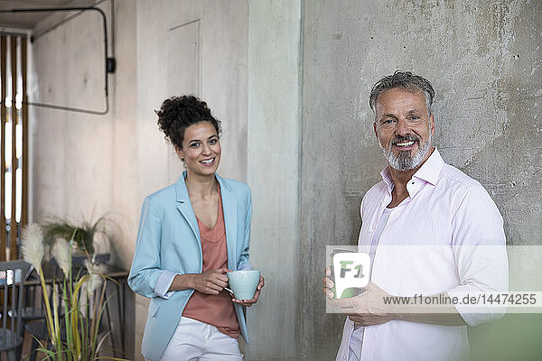 Porträt eines lächelnden Geschäftsmannes und einer Geschäftsfrau bei einer Kaffeepause in einem Loft
