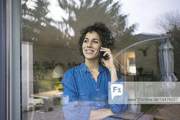 Porträt einer lächelnden Frau am Handy hinter dem Fenster zu Hause
