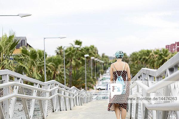 Spanien  Rückenansicht einer jungen Frau mit blau gefärbtem Haar mit Rucksack  die auf einer Brücke geht