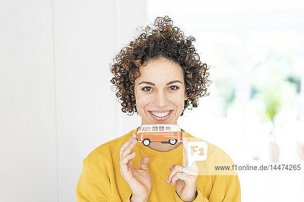 Porträt einer lächelnden Frau mit einem Wohnmobil-Modell