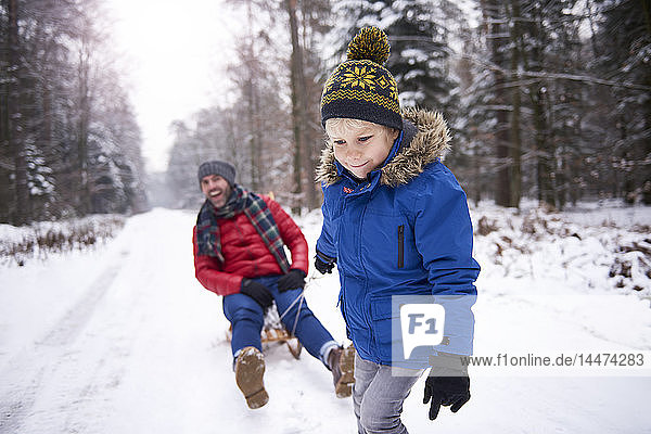 Portrait of little boy pulling his father sitting on sledge