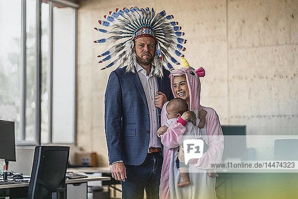 Mann und Frau  als Indianer und Einhorn verkleidet  im Amt stehend  Frau mit Baby im Arm