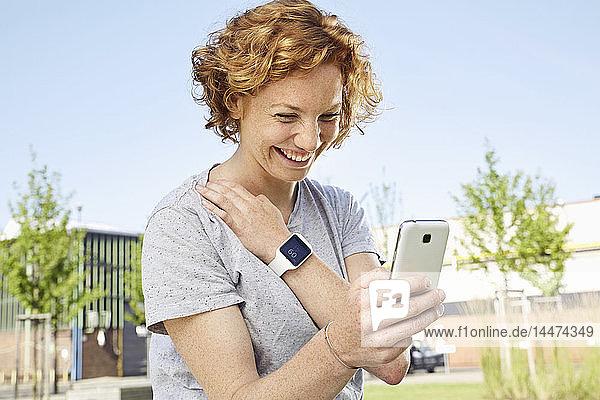 Glückliche junge Frau mit Smartwatch und Smartphone in städtischer Umgebung