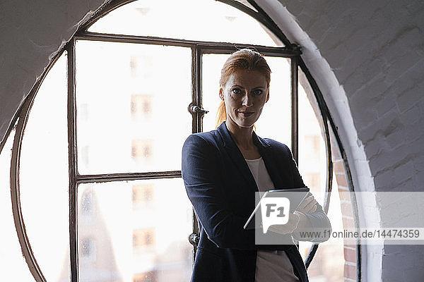 Porträt einer selbstbewussten Geschäftsfrau mit Tablette am Fenster