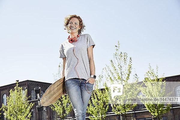 Lächelnde junge Frau mit Longboard  Kopfhörer und Smartwatch steht in städtischer Umgebung